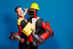 Industrie 4.0: Mensch trift Roboter in der modernen Arbeitswelt Studioportrait von Valery Kloubert, Koeln